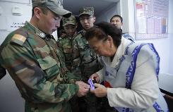 An election official checks a Kyrgyz soldier's thumb at the polling station in Bishkek on Sunday.