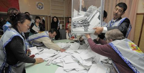 Members of an electoral committee sort through a ballot box Sunday at a polling station in Bishkek, Kyrgyzstan.
