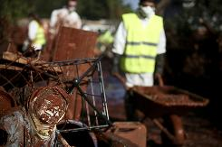 Rescue workers in Hungary push a wheelbarrow past mud-covered objects on Saturday.