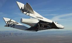The Virgin Galactic SpaceShipTwo, or VSS Enterprise,  glides toward the earth on its first test flight after release from the mothership, WhiteKnight2, over the Mojave, Calif., area, Sunday.