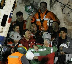 The last of the 33 Chilean miners to be rescued, Luis Urzua, embraces Chilean President Sebastian Pinera after being brought to the surface from the San Jose mine, near Copiapo, Chile.
