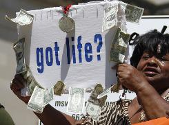 Civil rights activist Dorothy Benford of Jackson waves a sign with $11 in singles hanging from it -- to protest the life sentences Jamie and Gladys Scott received for a robbery that netted that same amount -- during a rally in Jackson on Sept. 15.