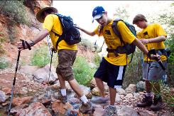 Chris Whitten, left, leads blind hiker Max Ashton, 14, across a stream with help from Tom Whitten, 15, as they make their way down the North Kaibab trail on the North Rim of the Grand Canyon during their 24-mile journey to the South Rim on Sunday.
