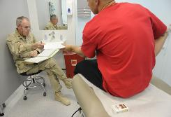 Navy Capt. Michael Wagner, the Traumatic Brain Injury director at a military base in Kandahar, Afghanistan, wraps up his examination of a soldier who was exposed to a bomb blast during combat operations. Although medical personnel currently lack a foolproof method of diagnosing concussions, the Army has been working on developing a blood test that can accurately detect them.