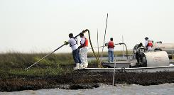 Teams of workers in hazardous material suits use vacuums to suck oil from marshes in Bay Jimmy, La.