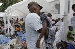 A man carries a sick child at the St. Nicholas hospital in Saint Marc, Haiti, on Thursday.