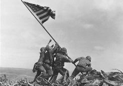 U.S. Marines of the 28th Regiment of the Fifth Division raise the American flag atop Mt. Suribachi, Iwo Jima, on Feb. 23, 1945. More than 6,000 Americans and 21,000 Japanese were killed in the battle.