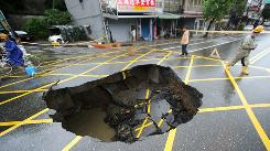 Residents walk past a hole in the road caused by flooding from Typhoon Megi in Suao, Taiwan, on Friday.