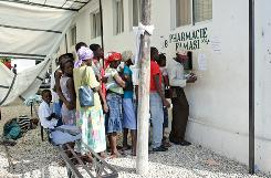 People line up to receive medicine from a pharmacy at St. Nicolas Hospital after a cholera outbreak hit the rural countryside, Friday, in St. Marc, Haiti.