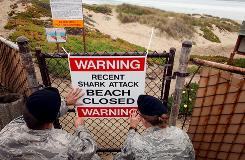 Airmen 1st class Daniel Clark, left, and Staff Sgt. Keri Embry post a sign warning surfers of a recent shark attack Friday at Vandenberg Air Force Base, Calif.