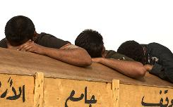 Three brothers of a man shot dead by a gunman in Baghdad on May, 17, 2006 sit next to his coffin as it is carried on top of a vehicle en-route to the funeral in Najaf, Iraq.