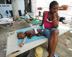 Cholera victims and families wait at St. Nicolas Hospital in St. Marc, north of Port-au-Prince, on Sunday.