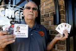 "Tom Lucas, shown here at Chiefs Wings, with playing cards and drink coasters featuring the faces and basic info of people missing in unsolved ""cold"" cases."