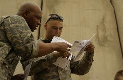 U.S. Army Cpl. Sean Morton, right, reviews his absentee ballot for the 2008 presidential election in Mosul, Iraq. There are about 4 million to 5 million military and overseas voters.