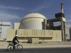 A worker rides a bike in front of the reactor building of the Bushehr nuclear power plant, just outside the southern city of Bushehr, Iran, on Tuesday.