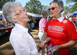 Carolyn Land, right, a volunteer for Steve Southerland, a Republican running for Congress, gives a brochure to Mary Howard on Saturday at the Florida Forest Festival in Perry, Fla.