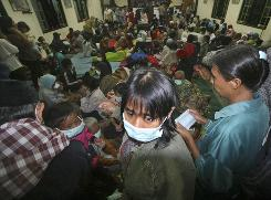 Villagers who live on the slopes of Mount Merapi wait after evacuation Tuesday at a temporary shelter in Indonesia.