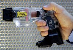 A Taser X26 shows Taser Cam attachment on the grip of the stun gun.