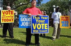 Jason Joseph, center, holds campaign signs at a get-out-the-vote rally last week by local unions and Democratic politicians in Miami. Early voting in Florida began Oct. 18.