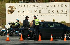 Members of the Prince William County (Va.) Police stand guard at the entrance of the National Museum of the Marine Corps on Friday in Triangle, Va. Gun shots were fired at the museum overnight when the building was not occupied.