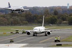 A jet lands near a United Parcel Service jet that is isolated on a runway at Philadelphia International Airport on Friday. Law enforcement officials are investigating reports of suspicious packages on cargo planes in Philadelphia and Newark, N.J.
