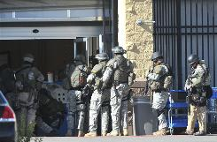 SWAT team members enter Walmart's garden shop entrance after a shooting at the Firecreek Crossing store in Reno on Friday.