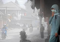 An Indonesian student covers her face with a mask to protect herself from Mount Merapi's volcanic ash on Saturday.