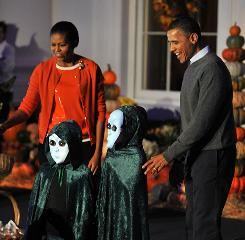 President Obama and first lady Michelle Obama hand out Halloween treats to local children and military families at the White House on Sunday.