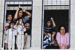 An ultra-orthodox Jewish family watch a protest against gender segregation in the neighborhood of Mea Shearim, from a window of their house in Jerusalem, Wednesday, Sept. 29, 2010. Orthodox Israelis and Jews from more liberal American branches of Judaism are at odds over laws affecting daily life in the Jewish state.