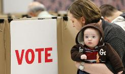 Daree Willman holds son Max, 5 months, as she votes Monday at the Oklahoma County Election Board in Oklahoma City.
