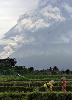 Farmers work on a field as Mount Merapi erupts Indonesia on Monday. It's Indonesia's most volatile volcano and one of 22 being closely watched following an increase in activity.