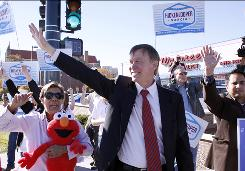 Colorado Democratic gubernatorial candidate John Hickenlooper waves at motorists as he and supporters do a honk and wave in Denver on Tuesday.