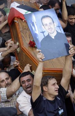 Mourners carry the coffin and photograph of slain Iraqi priest during his funeral in Baghdad on Tuesday. The priest was killed Sunday when gunmen stormed a church during mass.