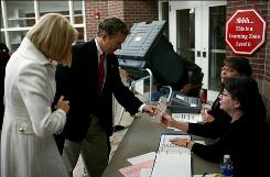 Kentucky Republican U.S. Senate candidate Rand Paul and his wife, Kelley, check in with election officials before casting their ballots in Bowling Green, Ky.