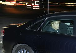 German leader Angela Merkel leaves her office after a suspicious package was discovered there on Tuesday.