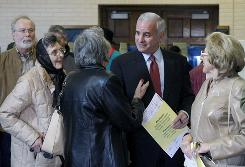 Gubernatorial candidate Mark Dayton talks with voters while waiting to enter his ballot near downtown Minneapolis.