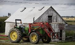 Lynn Hageman drives his tractor that has been upgraded with a roll bar on his farm near Calmar, Iowa.