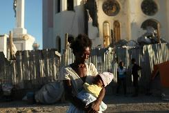 A woman and her child stand outside of the Cathedral of Our Lady of the Assumption church, which was destroyed in the January earthquake in Port -au-Prince. Haiti, one of the poorest nations in the Western Hemisphere, has been further unsettled by an outbreak of cholera, which has so far killed more than 330 people.