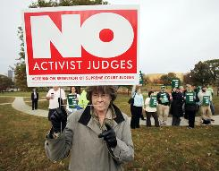 Dianne McGarey, of Ankeny, Iowa, holds up a sign during a rally of gay marriage opponents who wanted to remove three state Supreme Court justices.