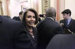 House Speaker Nancy Pelosi is surrounded as she goes to a television interview on Capitol Hill on Wednesday.