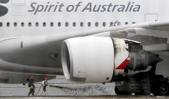 Firefighters surround a Qantas passenger plane which made an emergency landing with 459 people aboard in Singapore's Changi International Airport after having engine problems.