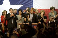 Re-Elected Governor Rick Perry celebrates Tuesday onstage with his family and other office holders who won re-election during his acceptance speech at the Texas Disposal Systems Exotic Game Ranch in Buda, Texas.