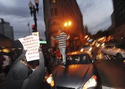 Oakland demonstrators jump on cars during protests Friday in reaction to the sentence of Bay Area transit officer Johannes Mehserle.