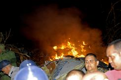 Flames emerge from the wreckage of a Cuban airliner as police officers and residents look on. The plane crashed near the village of Guasimal in Santi Spiritus province, Cuba, on Thursday.