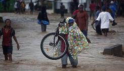 People wade through a flooded street Friday during the passing of Hurricane Tomas in Leogane, Haiti.