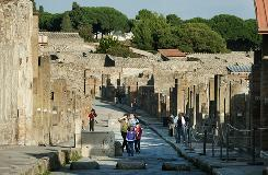 People walk on the Via dell'Abbondanza, one of the main streets of Pompeii.