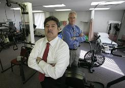 TheraMatrix CEO and owner Robert Whitton, left, and President Bob Read are battling Michigan's biggest insurer.