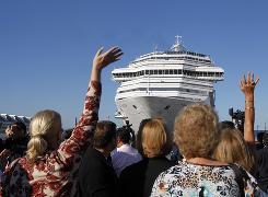 Spectators wave as the disabled Carnival Splendor cruise ship approaches the dock in San Diego on Thursday.