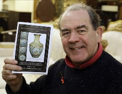 Auctioneer Peter Bainbridge holds up the Bainbridges auction catalogue showing the Chinese vase that he auctioned Thursday in London.