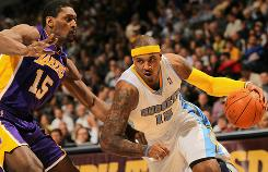 The Nuggets' Carmelo Anthony drives past Ron Artest of the Los Angeles Lakers on Thursday night in Denver. The Nuggets dealt the Lakers their first loss, winning 118-112.